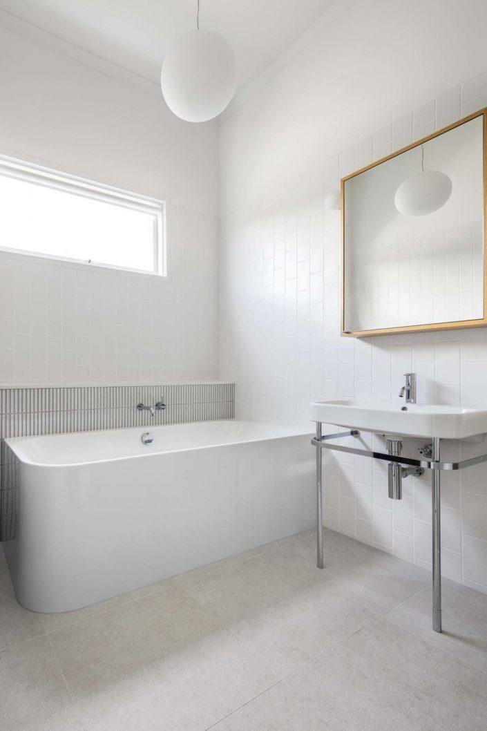 la salle de bain est toute en blanc avec une petite baignoire