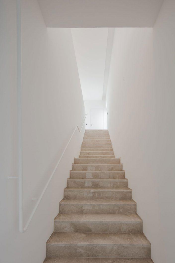 Des longs escaliers en pierre et murs blancs