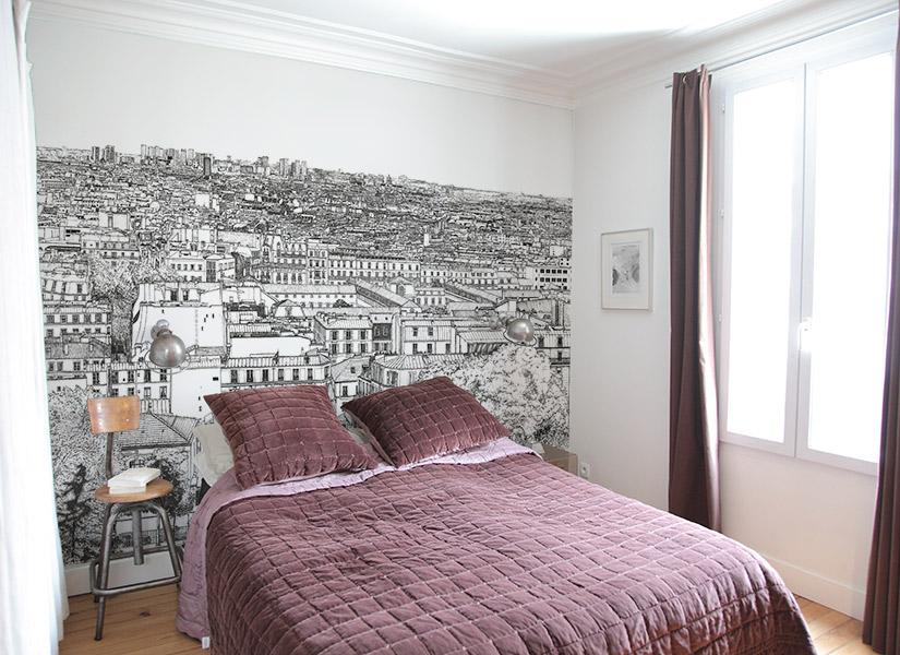 Une chambre avec un papier peint panoramique de Montmartre