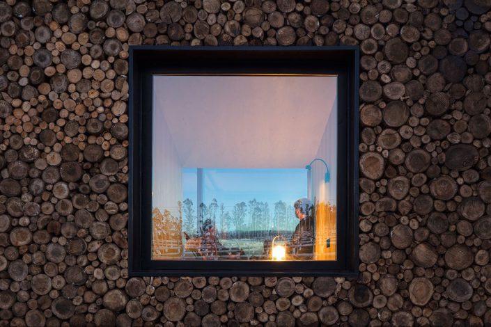L'autre façade parallèle à la baie vitrée est constituée de bûche de bois